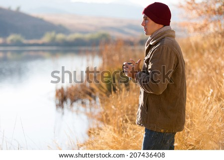 thoughtful man standing by lake and drinking coffee in autumn - stock photo