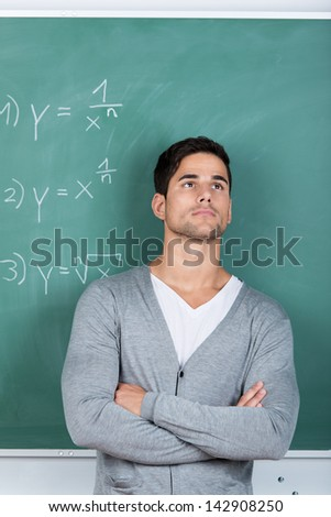 Thoughtful man standing with his arms folded in front of the chalkboard in a classroom with mathematical equations staring off into the distance