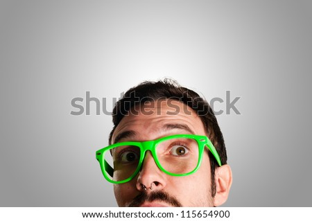 thoughtful man with green eyeglasses and gray background