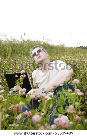 thoughtful man with laptop on meadow
