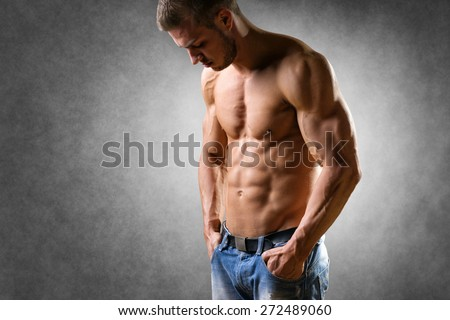 Thoughtful man with well trained body, biceps, abs and pecs and wearing a denim trousers
