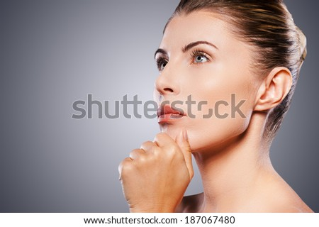 Thoughtful mature beauty. Side view of thoughtful mature woman holding hand on chin and looking away while standing against grey background - stock photo