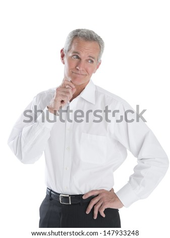 Thoughtful mature businessman looking away against white background - stock photo