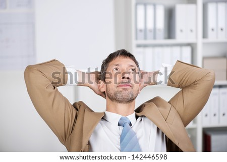 Thoughtful mature businessman with hands behind head looking up in office - stock photo