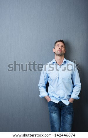 Thoughtful mature businessman with hands in pockets looking up against blue wall - stock photo