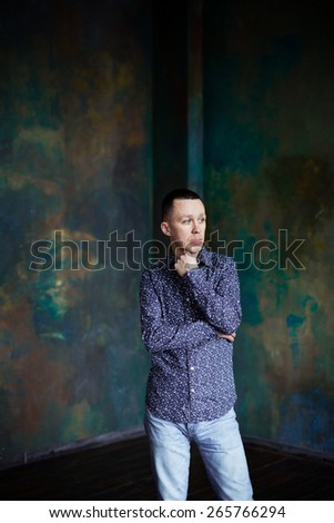 Thoughtful mature businessman with his hands behind his back wall - stock photo