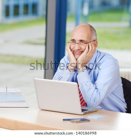 Thoughtful mature businessman with laptop looking away in office - stock photo