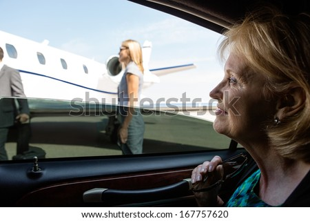 Thoughtful mature businesswoman in car looking at private jet - stock photo