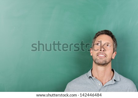 Thoughtful mature male teacher against blank blackboard - copy space for text - stock photo