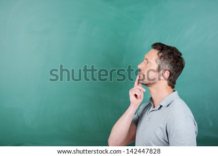 Thoughtful mature male teacher with hand on chin against blank blackboard - stock photo
