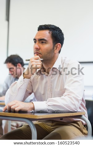 Thoughtful mature student taking notes with others in lecture in college - stock photo