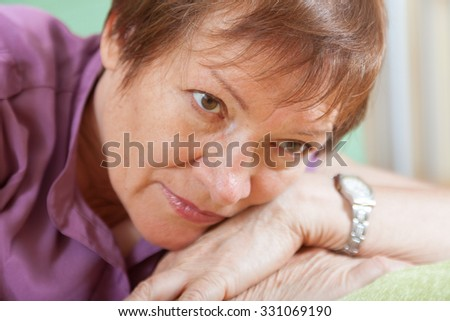 Thoughtful mature woman with sad face and in casual clothes laying on sofa  - stock photo