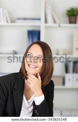 Thoughtful mid adult businesswoman with hand on chin looking away in office - stock photo