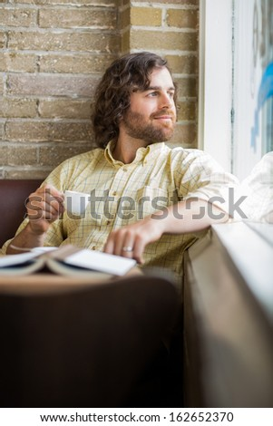 Thoughtful mid adult man with coffee cup looking through window in cafe - stock photo