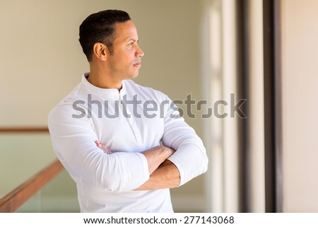 thoughtful mid age man with arms crossed at home