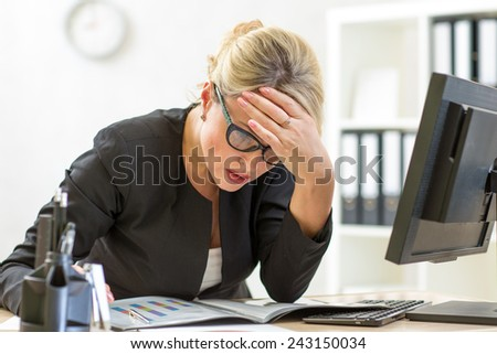 thoughtful middle-aged business lady looking at business papers in office - stock photo