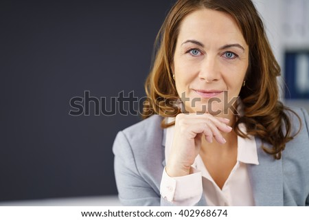 Thoughtful middle-aged businesswoman resting her chin on her hand and looking straight into the camera, close up head and shoulders portrait with copy space - stock photo