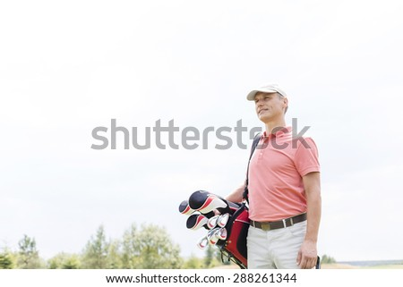 Thoughtful middle-aged golfer looking away while carrying bag against clear sky - stock photo