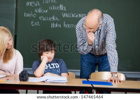 Thoughtful middle-aged male teacher in class standing over a young boy sitting at a desk reading something in a notebook - stock photo