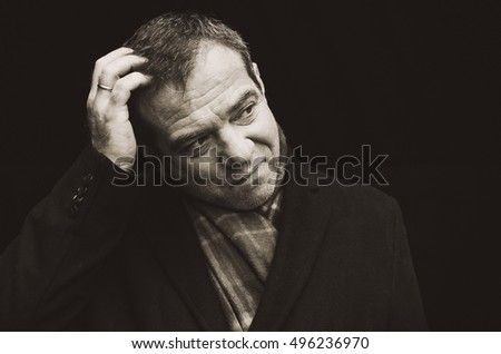 Thoughtful middle-aged man in a black coat. He rubs his hand in the back of the head. Black and white photography