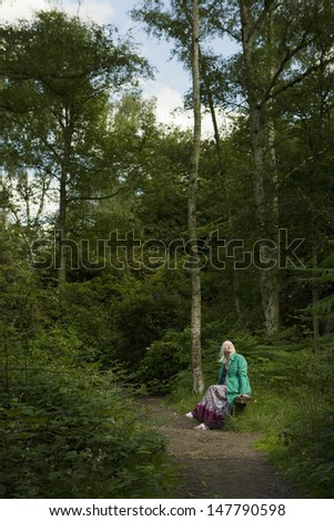 Thoughtful middle aged woman sitting on a bench beside path in forest - stock photo