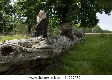 Thoughtful middle aged woman sitting on a dead tree - stock photo