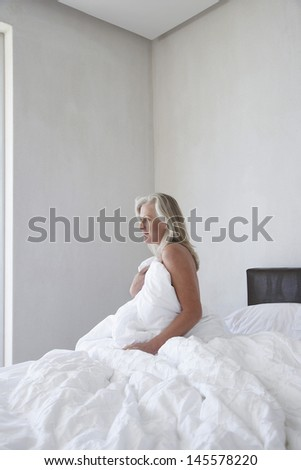 Thoughtful middle aged woman wrapped with duvet on bed