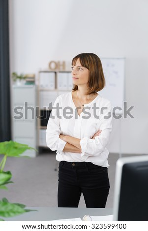 Thoughtful Office Woman Standing at her Desk and Looking Into the Distance with Arms Crossing Over her Chest. - stock photo