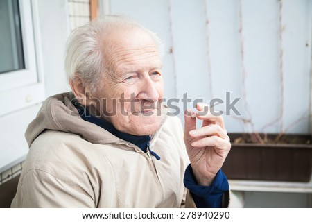 thoughtful old man smoking a cigarette and musing upon a distant scene - stock photo