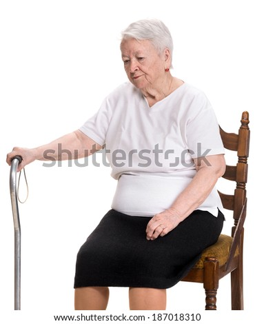 Thoughtful old woman  sitting in the chair on a white background - stock photo