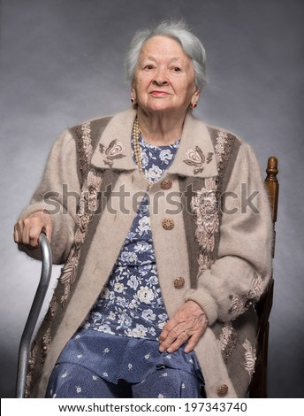 Thoughtful old woman sitting on the chair on a gray background - stock photo
