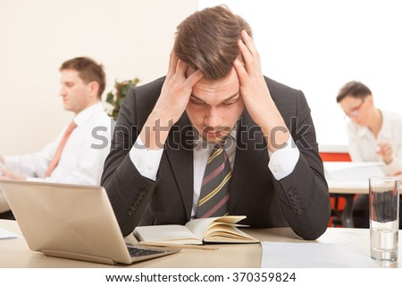 Thoughtful or stressful businessman at work in the office - stock photo