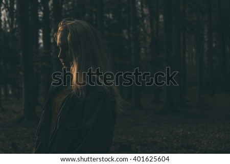 thoughtful portrait of a young woman standing in the wood, dark blue tint