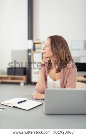 Thoughtful Pretty Office Woman Sitting at her Desk with Laptop and Notes, Looking Into Distance with Hand on her Chin.
