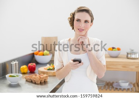 Thoughtful pretty woman holding her smartphone standing in her kitchen at home - stock photo