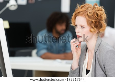 Thoughtful pretty young redhead businesswoman sitting at her desk staring at her computer monitor with her hand to her chin and a pensive expression - stock photo