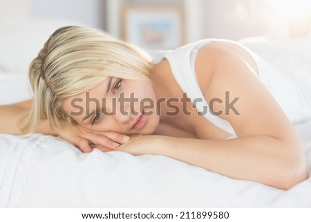 Thoughtful relaxed young woman lying in bed at home - stock photo