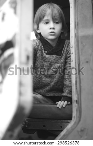 Thoughtful sad child sitting in a driver cabin of an old truck - stock photo