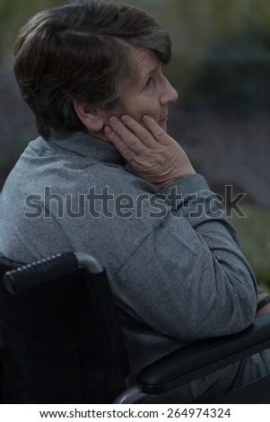 Thoughtful sad senior woman sitting in a wheelchair - stock photo