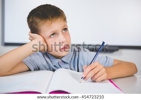 Thoughtful schoolboy doing homework in classroom at school - stock photo
