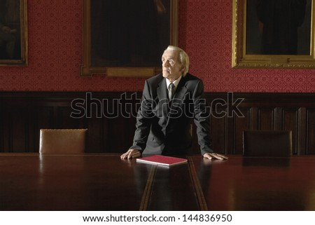 Thoughtful senior businessman leaning hands on conference table