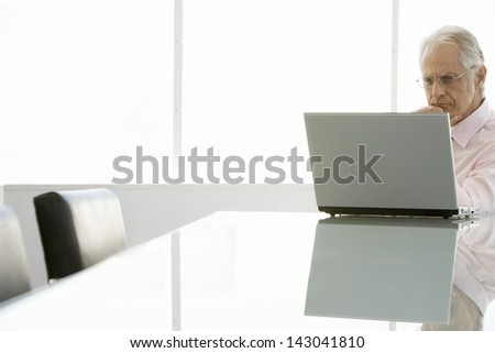 Thoughtful senior businessman looking at laptop in conference room - stock photo