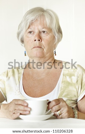 Thoughtful Senior lady sitting at table holding a cup of tea