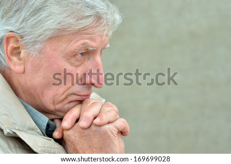 Thoughtful senior man at grey outdoor background - stock photo