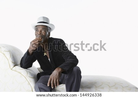 Thoughtful senior man in fedora sitting on chaise lounge against white background - stock photo