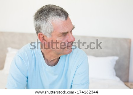 Thoughtful senior man looking away while sitting on bed at home