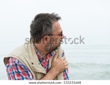 Thoughtful senior man posing at the beach on a foggy day