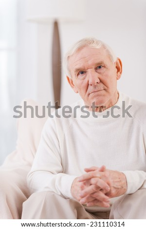 Thoughtful senior man. Serious senior man holding fingers crossed on his hands and looking at camera while sitting in chair  - stock photo