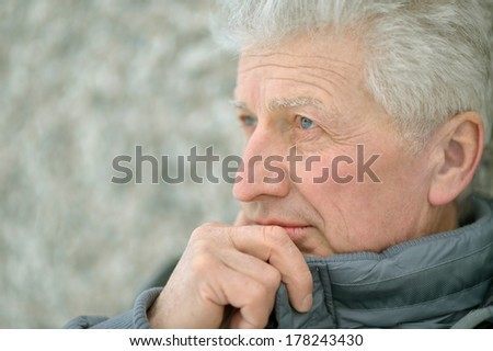 Thoughtful senior man standing outdoor in warm winter clothes