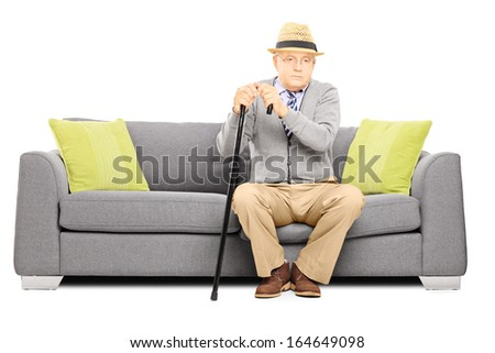 Thoughtful senior man with a cane sitting on a sofa isolated on white background - stock photo